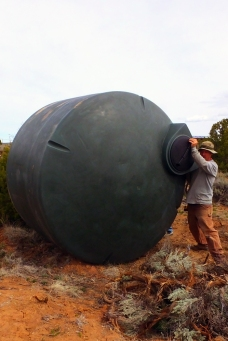 Rolling water cistern into place